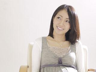 笑顔で椅子に座る妊婦