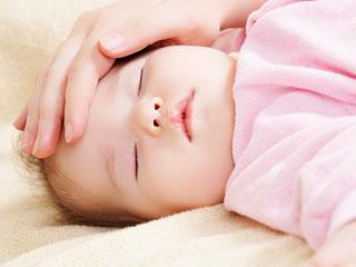 赤ちゃんの額に掌を当てて熱を調べる