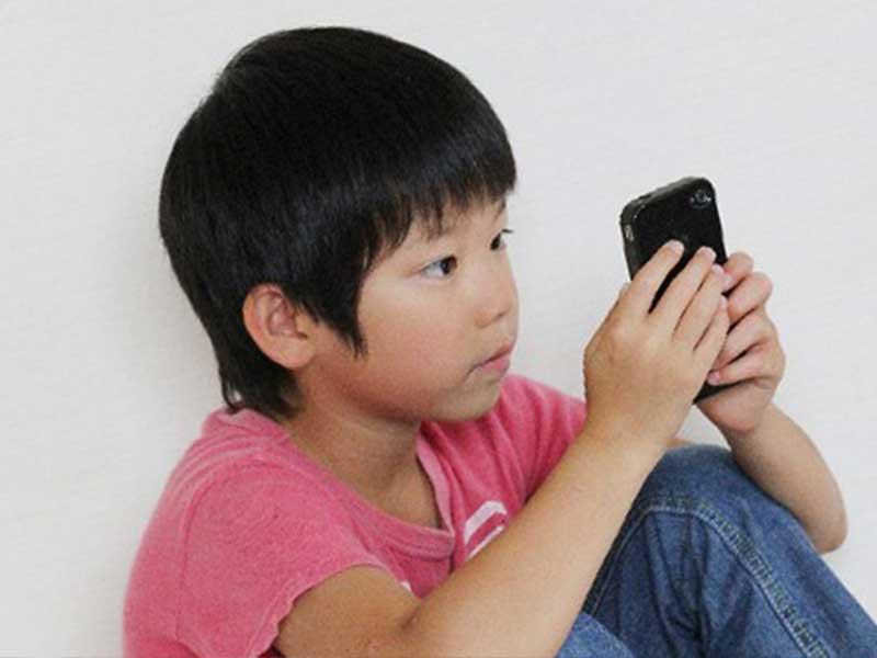 スマホでゲームを見る少年