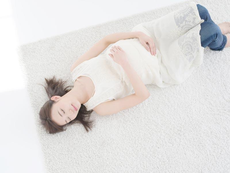 仰向けになって寝ている若い妊婦さん