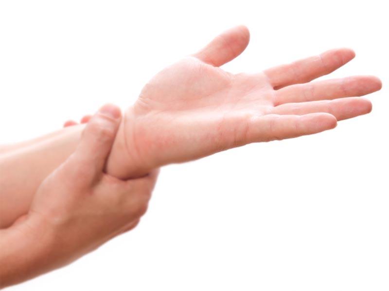 自分の手首を気にして触っている女性