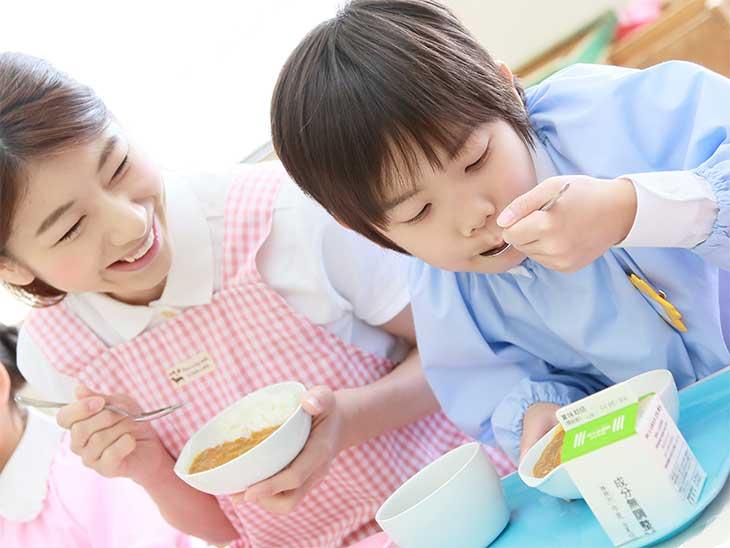 幼稚園で給食を食べている男の子とそれを見守っている保育士さん