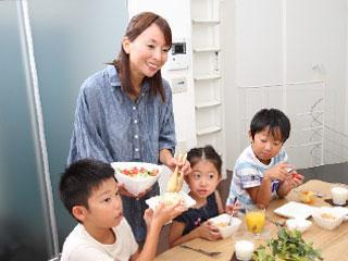 笑顔で子供達に食事をするママ