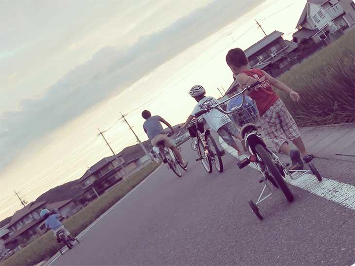 夕暮れ時に自転車に乗ってる家族の後ろ姿