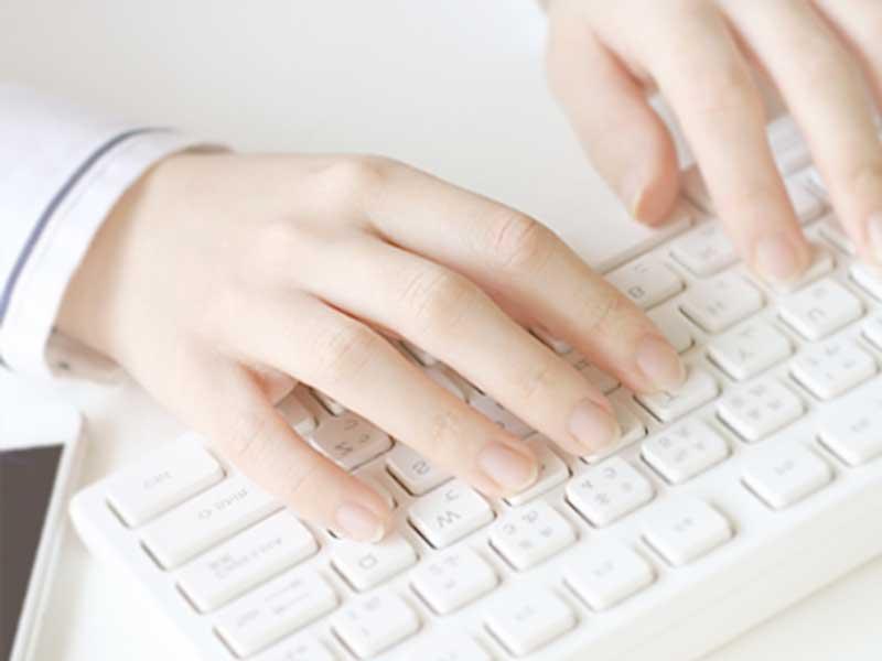 パソコンで調べる女性の手