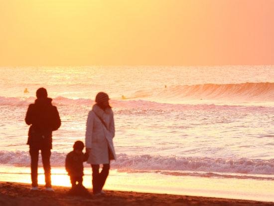 海で夕日を見ながら景色を眺める3人の家族