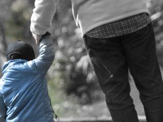 子供と手をつないで歩くパパ