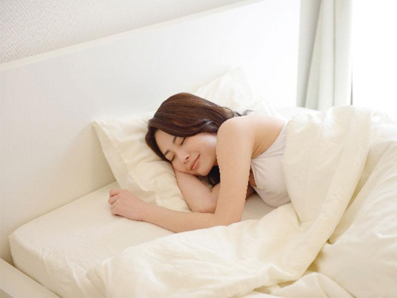 ベッドでぐっすり寝る女性