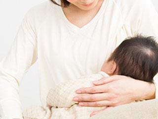 赤ちゃんを胸に抱く母親