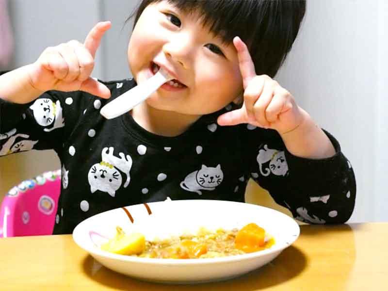 カレーをスプーンで食べてる女の子