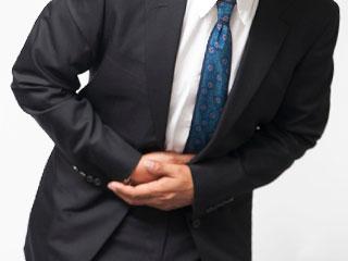 お腹を押さえるスーツ姿の男性