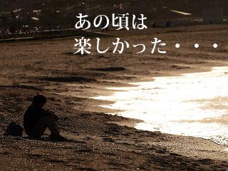 夜の砂浜に一人で座る男性のシルエット