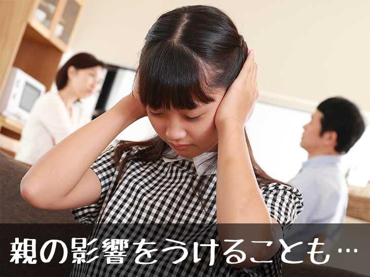 親の喧嘩を耳を塞いで聞かないようにしている女の子
