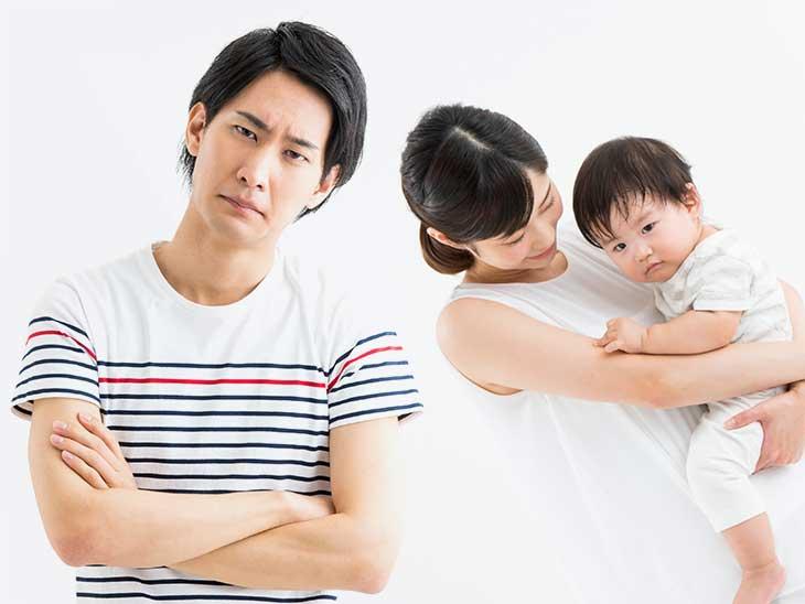 赤ちゃんを抱っこしているママに相手にされず困り顔のパパ