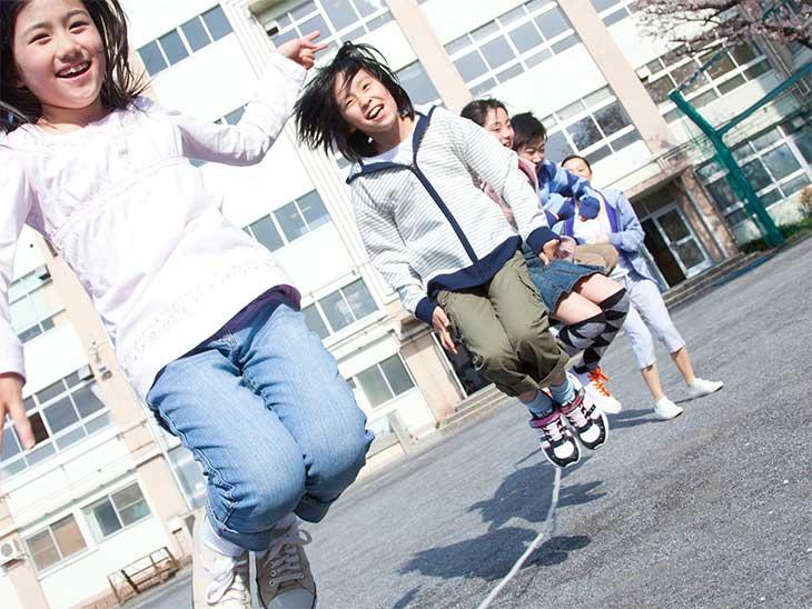 学校の校庭で縄跳びで遊んでいる小学生たち