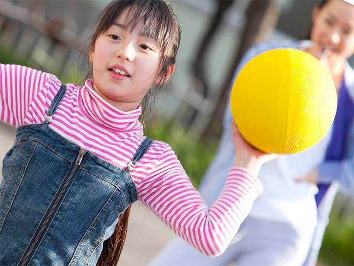 休憩時間に校庭でドッジボールをしている女の子