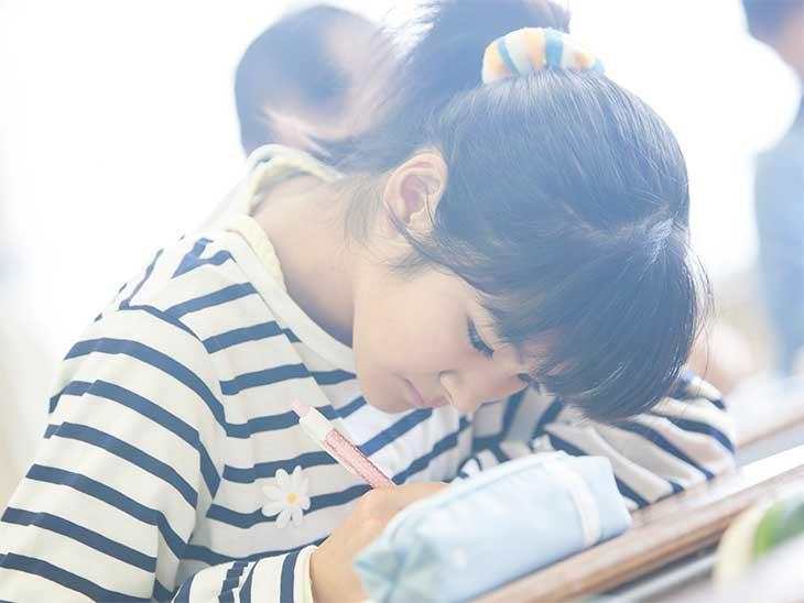 小学校の休憩時間に自分の席で絵を描いている女の子