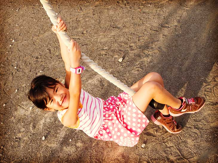公園のロープ遊具で遊んでいる腕時計をした女の子