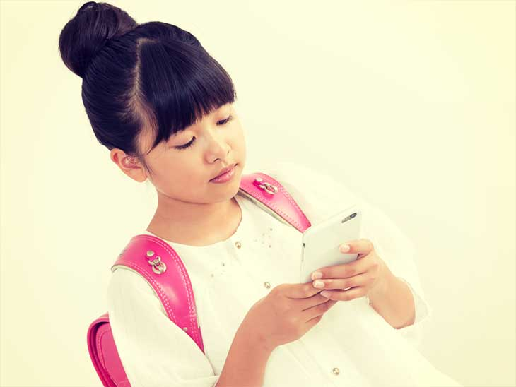 携帯電話で母親に連絡しようとしている女の子