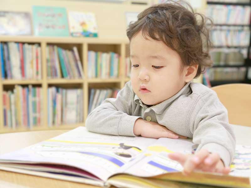 テーブルで絵本を読む子供