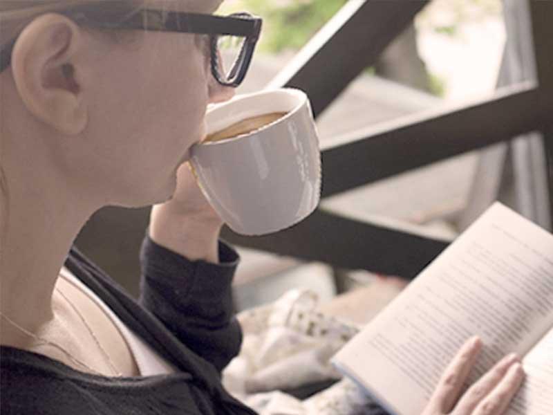 コーヒーを飲みならが勉強する母親
