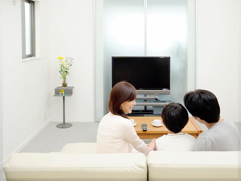 ソファに座って子供と話し合う両親