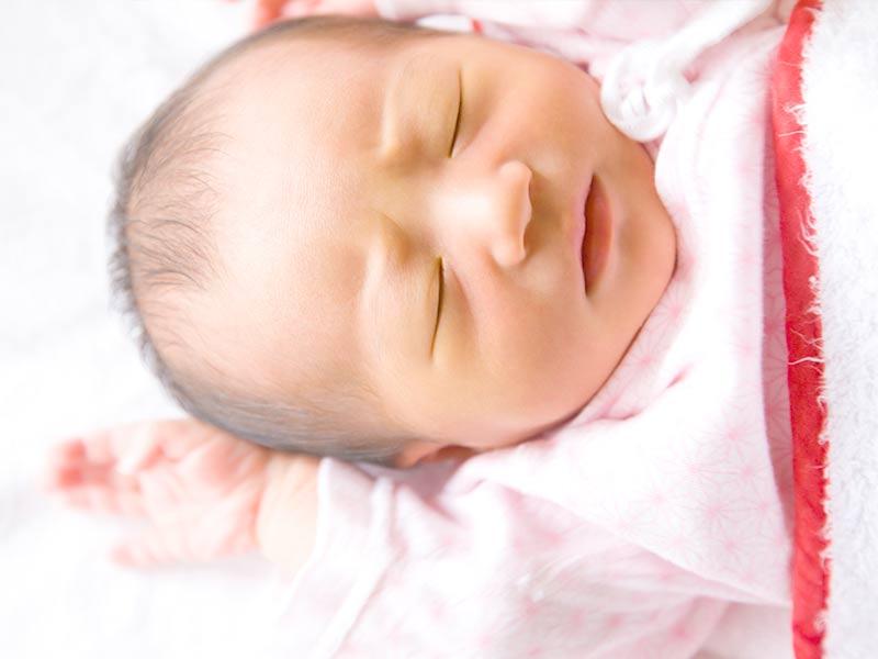 布団の上にでぐっすり寝る赤ちゃん