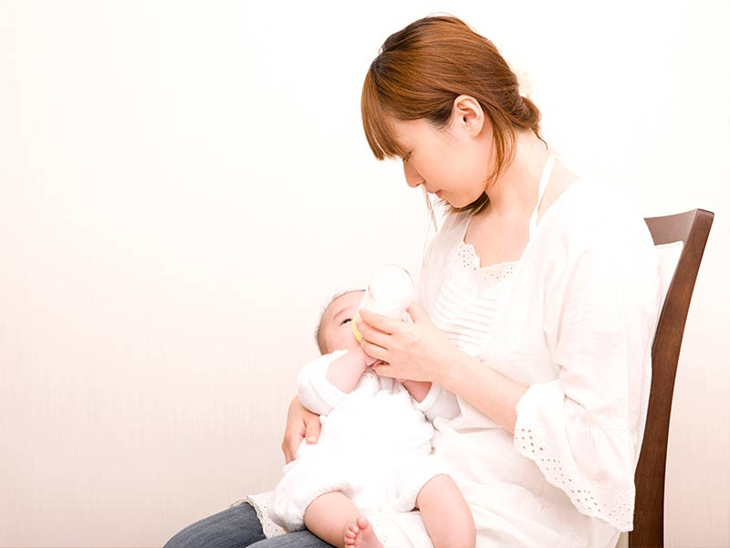 赤ちゃんに哺乳瓶からミルクを飲ませるお母さん