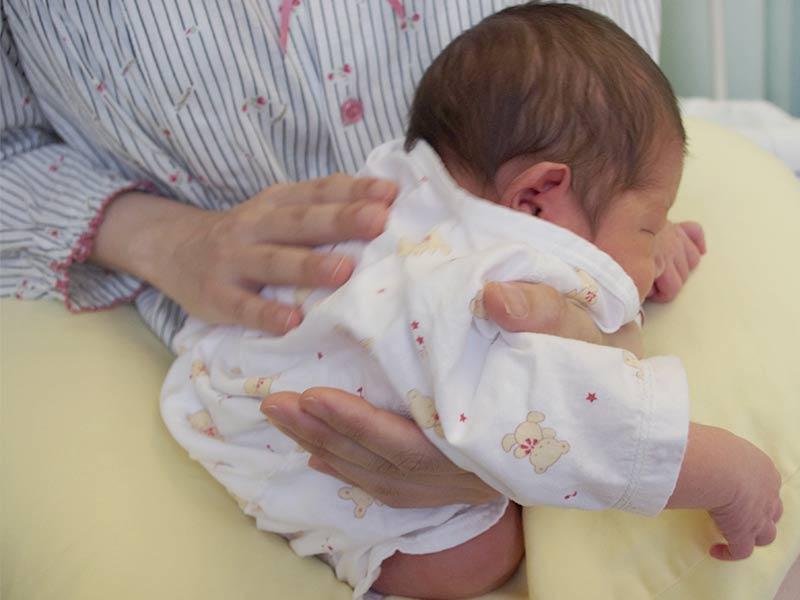 ママにげっぷをさせられる赤ちゃん