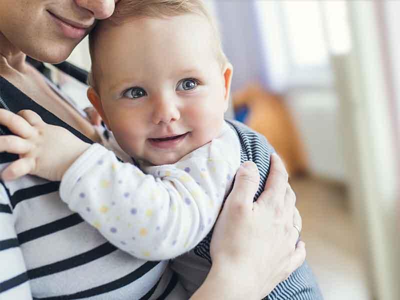 抱っこ紐を使って笑顔の赤ちゃんを抱っこしてるママ