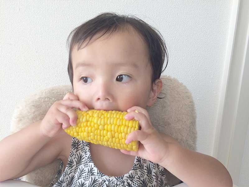 トウモロコシを食べる1歳児