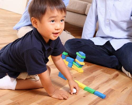 親と一緒に居間で遊ぶ幼児