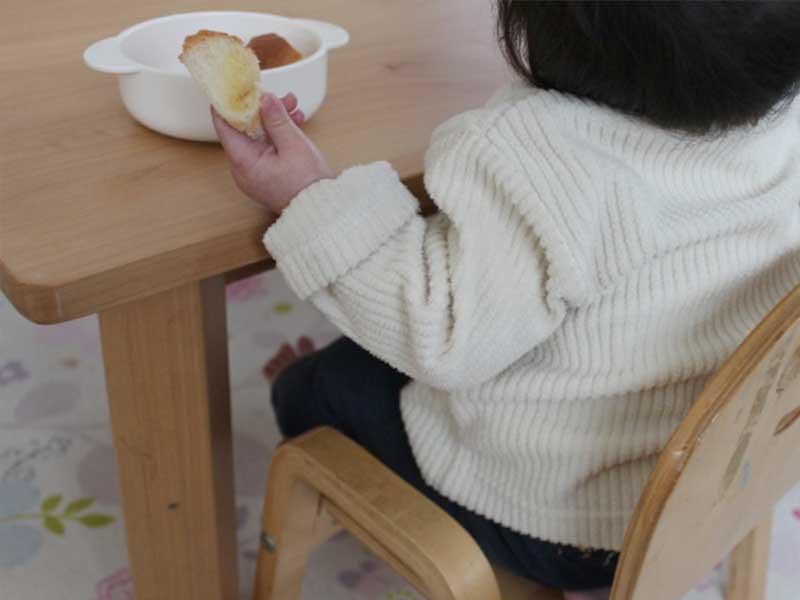 イスに座りながらパンを食べる赤ちゃん