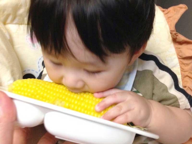 トウモロコシ食べる子供