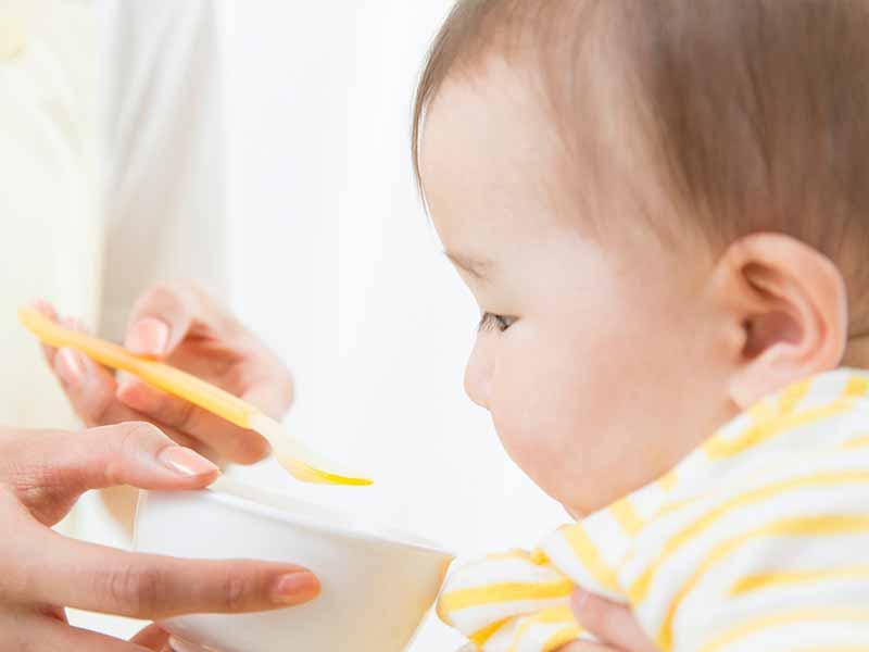 スプーンで離乳食を食べる赤ちゃん