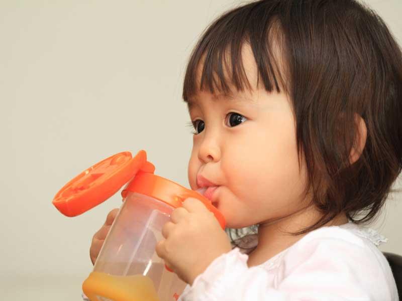 ストローマグでジュースを飲んでいる赤ちゃん