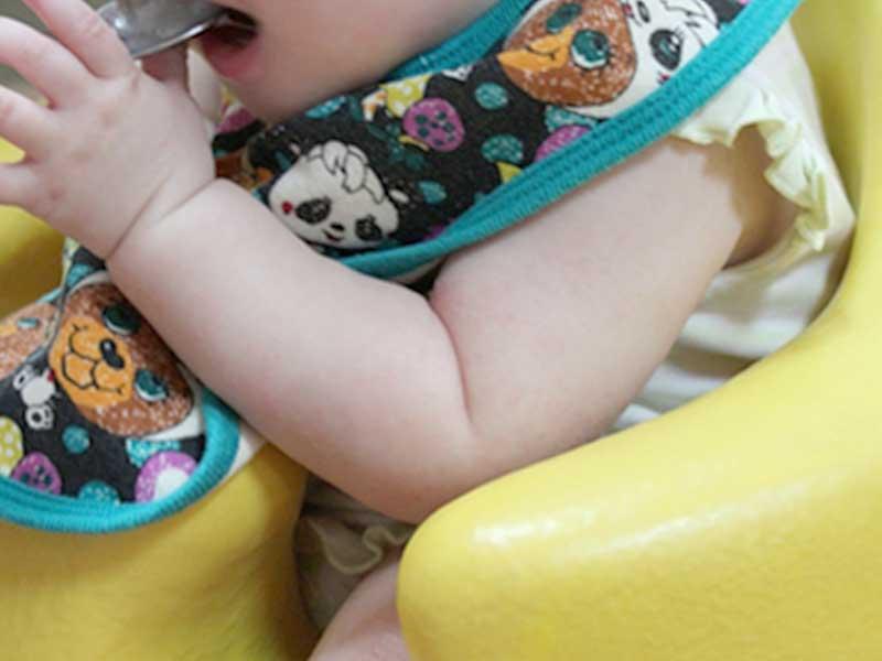 イスに座って離乳食を食べる赤ちゃん