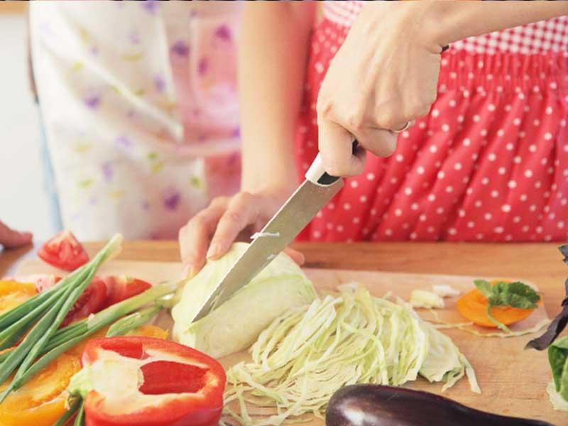 包丁で野菜を切る女性