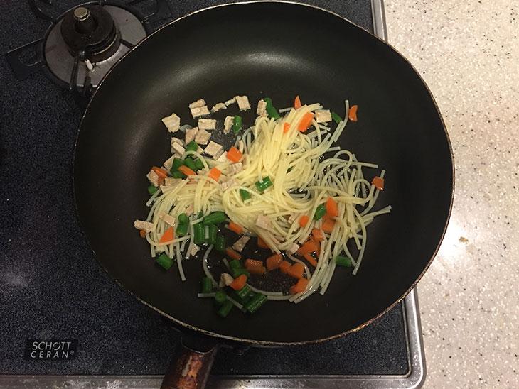 フライパンでパスタと人参と豚肉とさやいんげんを炒める
