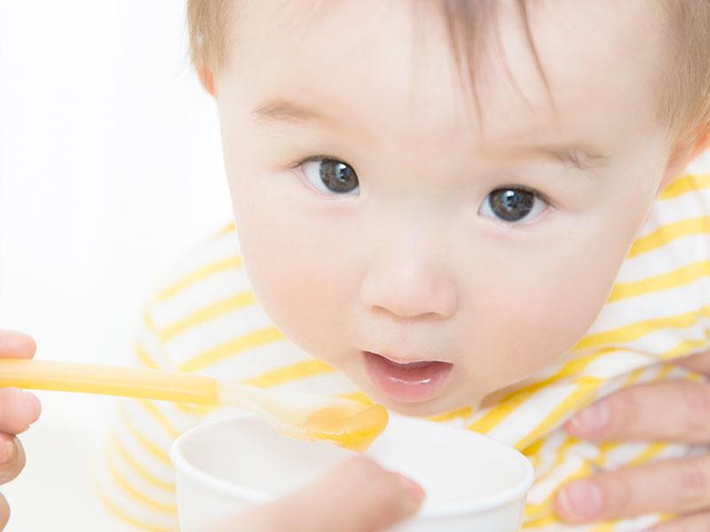 黄色いスプーンで離乳食を食べる赤ちゃん