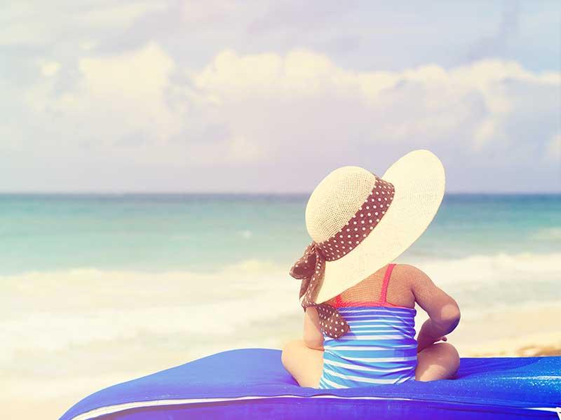海にいる日焼けしないように帽子をかぶった赤ちゃん