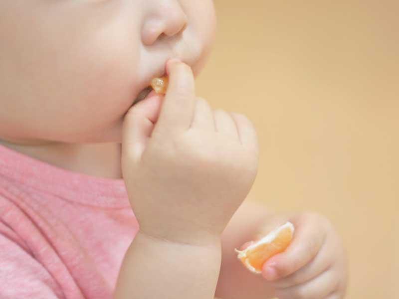 みかんを食べる小さい男の子