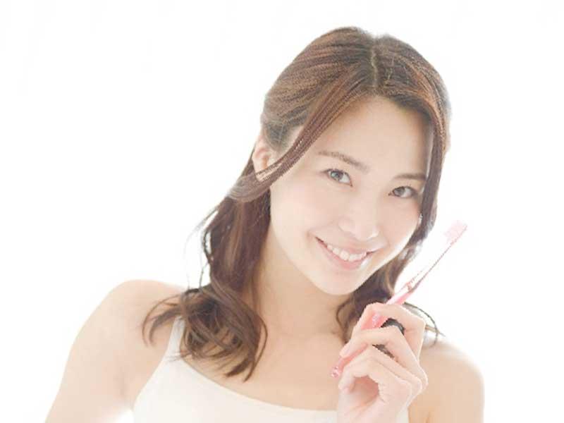 歯ブラシきを持つ女性