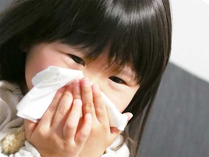花粉症で鼻を洟をかんでいる女の子