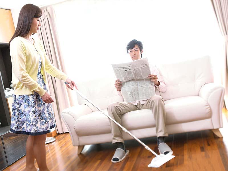 奥さんが掃除をしている目の前で新聞を読む旦那さん