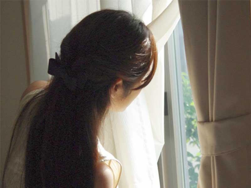 窓から外を見ている奥さん