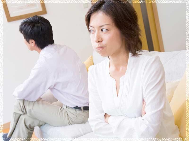 ソファに座る喧嘩中の夫婦