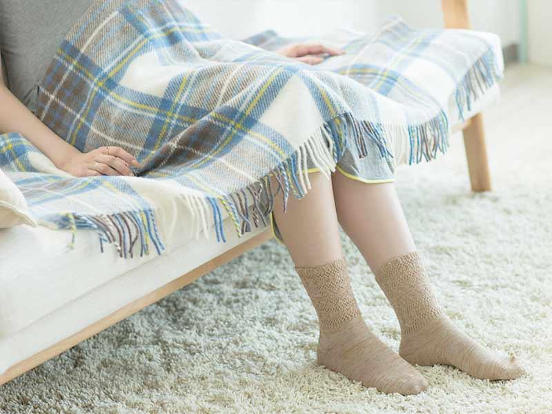 ソファに座って休んでいる妊婦さん