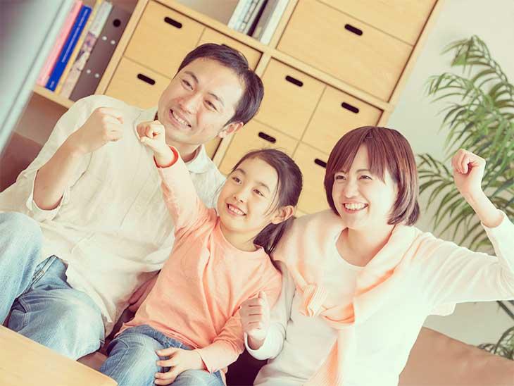 両親と一緒に笑顔でテレビを見ている女の子