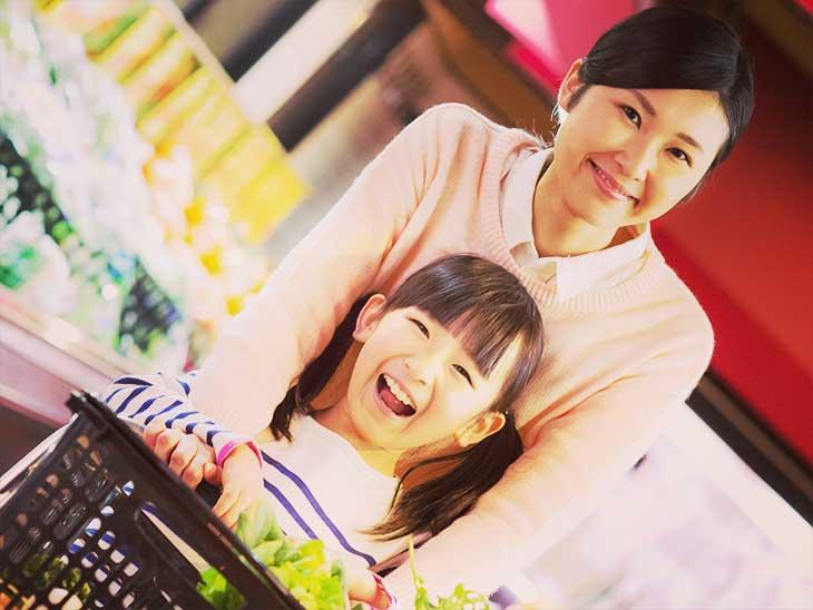 母親と一緒にスーパーのカートを押して買い物をしている女の子